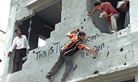 Palestinians graffiti a building in Gaza City after an Israeli air raid