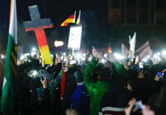 Participants hold up their mobile phones during a demonstration called by anti-immigration group PEGIDA in Dresden