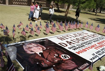 People protesting against Senate Bill 1070 walk past a banner depicting Arizona's Governor Brewer as a Nazi outside the Arizona State Capitol in Phoenix