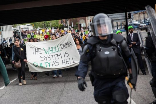 BALTIMORE, MD - MAY 01: Protesters march through the streets in support of Maryland state attorney Marilyn Mosby's announcement that charges would be filed against Baltimore police officers in the death of Freddie Gray on May 1, 2015 in Baltimore, Maryland. Gray died in police custody after being arrested on April 12, 2015. (Photo by Andrew Burton/Getty Images)