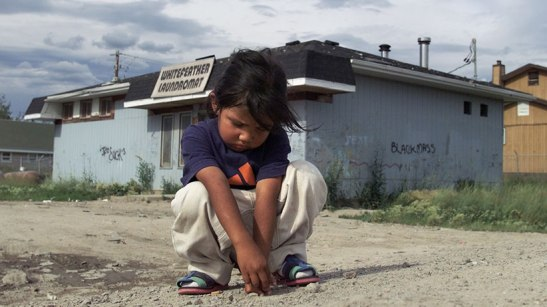 Pikangikum_SadGirl50-07/24/01-A sad young girl plays by herself on a dusty road in Pikangikum. Pikangikum First Nations is located in Ontario, 300km north west of Winnipeg, and also has the highest suicide rate in the world. (BERNARD WEIL/TORONTO STAR) DIGITAL IMAGE BERNARD WEIL/TORONTO STAR/CP