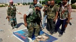 FILE - In this Saturday, Sept. 22, 2012 file photo, a Free Syrian Army fighter from the Al-Faruk brigade, center, steps on a portrait of Syrian President Bashar Assad, at the Tal Abyad, a Turkish-Syrian border crossing captured by the rebels earlier in the week, eastern Syria. (AP Photo/Hussein Malla, File)